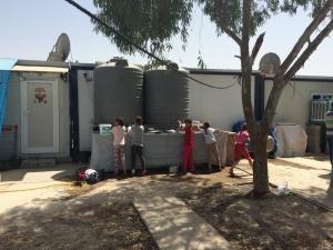 Přístup k vodě je v některých táborech společný pro desítky uprchlíků, podobně jako toalety. Na snímku děti myjí nádobí, foto: GEN21