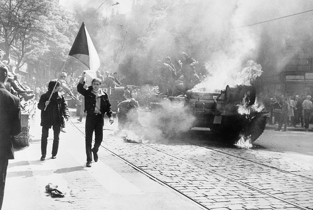 During the Soviet invasion of Czechoslovakia Czechoslovaks carry their national flag past a burning tank in Prague photo from CIA Analysis of the Warsaw Pact Forces