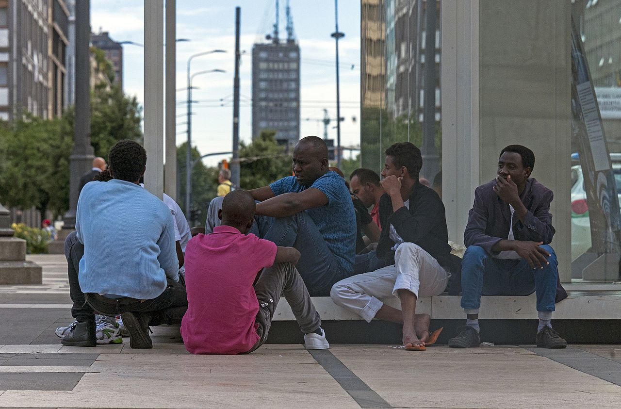 Daniel Case African men sitting on the Piazza duca dAosta Milan