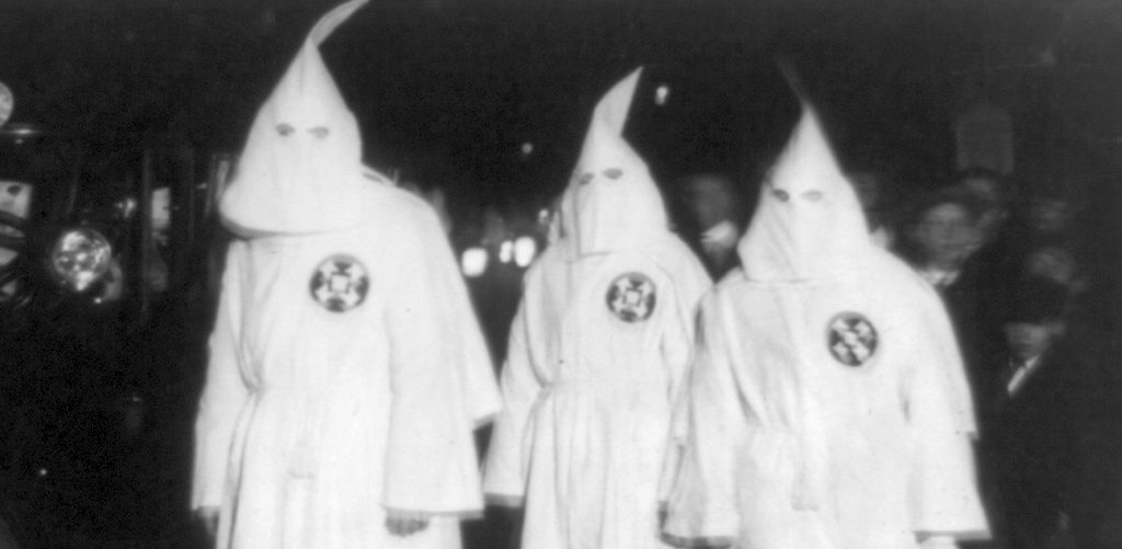 Three Ku Klux Klan members standing beside automobile driven by Klan members at a Ku Klux Klan parade through counties in Northern Virginia bordering on the District of Columbia Library of Congress
