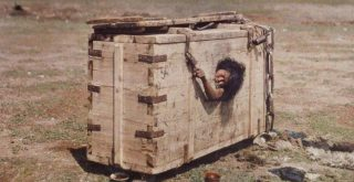 A Mongolian woman reaches out from the porthole of a crate in which she is imprisoned by Stephane Passet